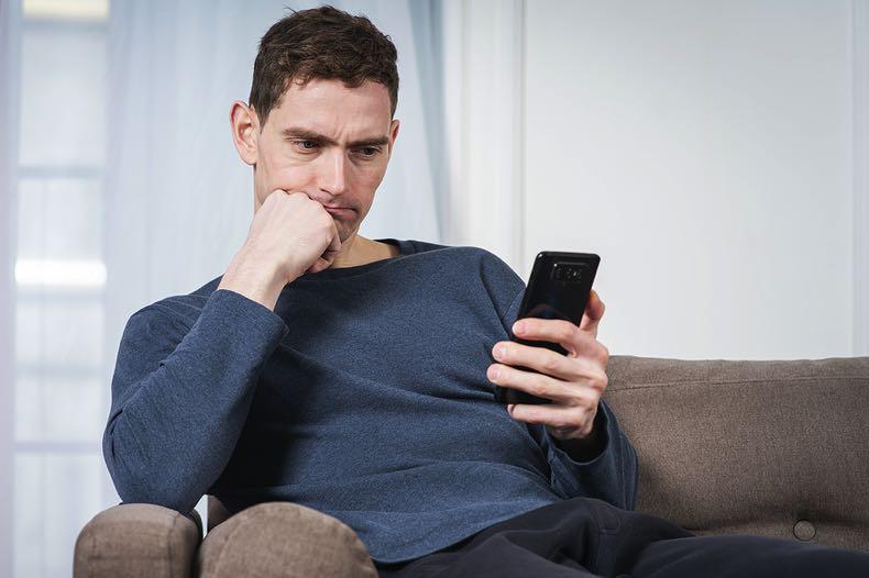 Man thinking staring at his mobile