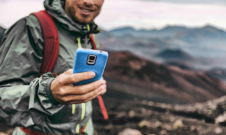 Man hiking on his phone
